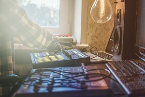 close up man making music in the home studio using drum machines