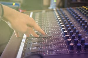 close up hand adjusting volume on music recording panel with faders
