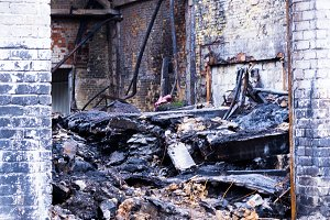 Entrance to the room that burned. Building after the fire. Broken walls and roof.
