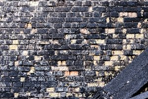 Brick wall after the fire. The fallen beam. Dramatic background.