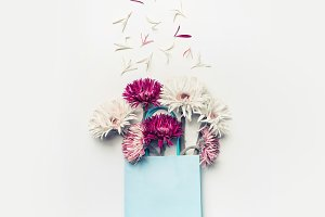 Flowers in blue paper shopping bag