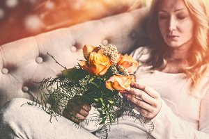 Woman on sofa with Roses bunch