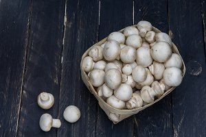 White champignons in a wooden basket. Black wooden background.