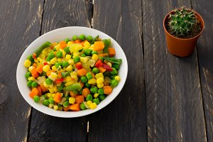 A plate with Mexican salad and a cactus on a black background. A colorful salad.
