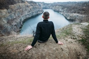 man relax on rocky cliff