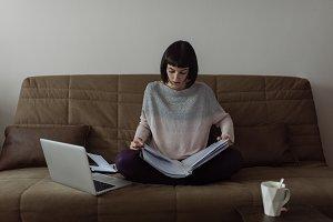 Young beautiful woman sitting on sof