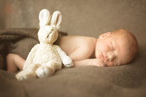 Sweet newborn baby sleeps with toy on grey background. Copy space for your text. Maternity, family, birth concept.