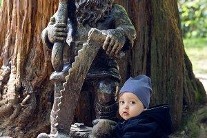 child sits with a tree and a wooden sculpture