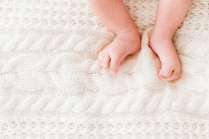 Baby's feet on knitted background