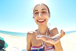 Attractive smiling woman with healthy skin applying sunscreen on the sunny beach
