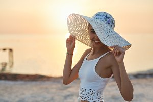 beautiful sexual woman in white hat and bikini against the sea and sunset