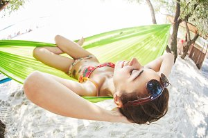 young happy woman in a hammock on the beach