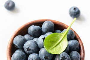 Blueberries with green leaf in bowl