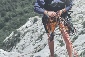 man rock climber on the top of the cliff and belays a partner
