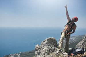 man rock climber stands on the top of the cliff