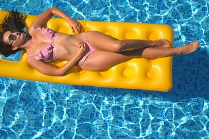 Top view of beautiful tanned girl in sunglasses and pink bikini lying on yellow inflatable mattress in swimming pool. Young woman relaxing in basin of hotel during summer travel. Concept of vacation