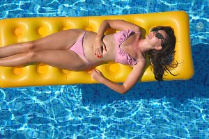 Beautiful girl in sunglasses and bikini lying on yellow inflatable mattress in swimming pool. Young tanned woman relaxing in basin of hotel on sunny day. Concept of summer vacation. Top view Close up