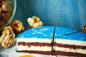 half of cutted mousse cake with blue glaze on a dark gray concrete table and blue background