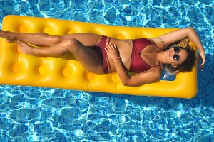 Beautiful girl in sunglasses and red bikini lying on yellow inflatable mattress in swimming pool. Young tanned woman relaxing in basin of hotel on sunny day. Concept of vacation. Top view Close up