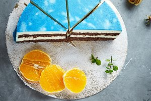 half of cutted mousse cake with blue glaze on a dark gray concrete background