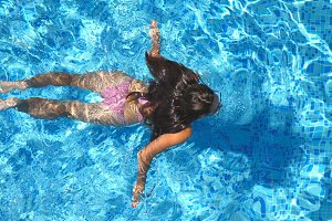Unrecognizable beautiful girl floating across the pool of hotel. Young woman swimming in clear blue water of basin on sunny day. Concept of summer vacation or holiday. Top view Close up Slow motion