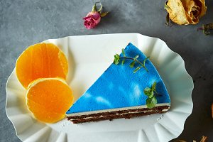 piece of cutted mousse cake with blue glaze on a dark gray concrete background