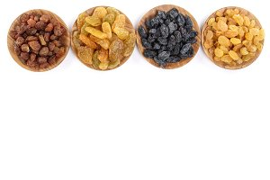 Collection of raisins in wooden bowl isolated on a white background with copy space for your text. Top view. Flat lay