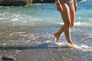 Legs of young girl going along sea pebble beach on sunny day. Gentle waves splashing over female feet walking barefoot on seashore. Beautiful woman in bikini enjoying summer travel. Close up
