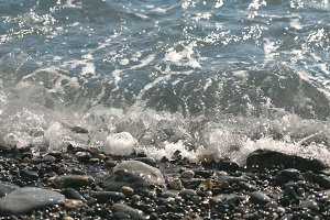 Calming scene of gentle waves splashing to pebble beach on sunny day. Beautiful seascape at background. Concept of vacation or holiday. Close up Slow motion