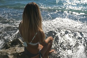 Rear back view of unrecognizable young girl in bikini sitting on stone near seashore and looking into distance on sunny day. Sunlight reflecting at the water surface at background. Vacation concept