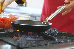 Unrecognizable chef cooking vegetarian dish on pan for breakfast in the hotel restaurant. A male cook frying vegetables on flaming skillet at morning for tourist. Meal preparation concept. Close up