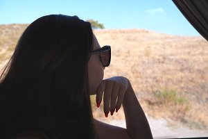 Girl in sunglasses watching out the window during trip. Young woman traveling by bus at summer and looking to window. Female tourist takes a autobus ride. Vacation or excursion concept. Close up