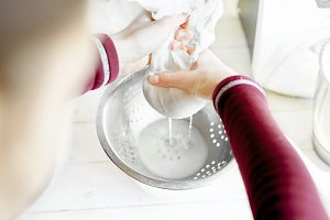 woman preparing almond milk at home.