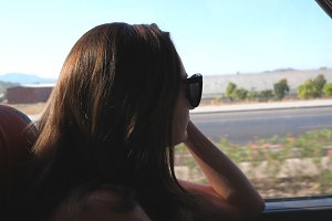 Female tourist takes a autobus ride. Vacation or excursion concept. Young woman traveling by bus at summer and looking to window. Girl in sunglasses watching out the window during trip. Close up