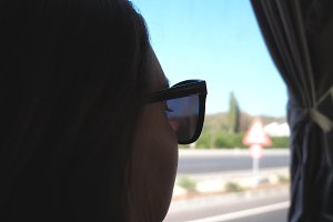 Profile of young woman traveling by bus at summer and looking to window. Girl in sunglasses watching out the window during trip. Female tourist takes a autobus ride. Vacation or excursion concept