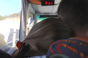 Young couple traveling by bus at summer. Unrecognizable girl hugging her boyfriend during trip. Pair of tourists takes a autobus ride. Vacation or excursion concept. Close up Rear back view