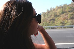 Young woman traveling by bus at summer and looking to window. Girl in sunglasses watching out the window during trip. Female tourist takes a autobus ride. Vacation or excursion concept. Close up
