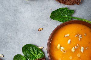pumpkin cream soup and product set on the blue dish on the concrete backdrop