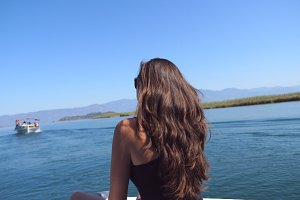 Rear back view of young girl sitting on bow of boat and looking to beautiful nature landscape during trip. Happy woman enjoying summer travel. Vacation or holiday concept. Close up Slow motion