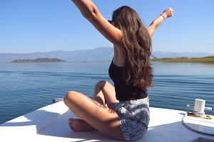 Young girl sitting on bow of boat, looking to beautiful nature landscape and raising hands to enjoy freedom. Happy woman enjoying summer travel. Vacation or holiday concept. Close up Slow motion