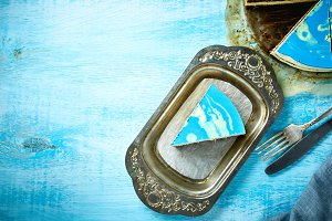 sliced cake and piece of mousse cake with blue glaze on a looking like silver, vintage metal dish on the white-blue wooden background