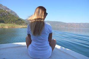 Rear back view of young girl sitting on bow of boat and looking to beautiful nature landscape on sunny day. Happy woman with blonde hair enjoying summer travel. Vacation or holiday concept. Close up