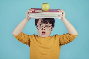surprised boy with books and apple