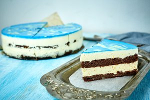 piece of mousse cake with blue glaze on a looking like silver, vintage metal dish on the white-blue wooden table