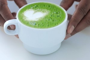 Matcha tea preparation in cafe by mixed race barman