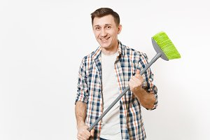 Young smiling happy housekeeper man in checkered shirt holding and sweeping with green broom isolated on white background. Male doing house chores. Copy space for advertisement. Cleanliness concept.