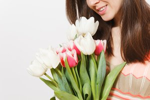 Close up cropped portrait of bright bouquet of white and pink spring tulips in hand of young smiling brunette girl in patterned dress in studio on white background. Concept of celebration, good mood