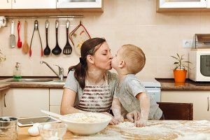 Little kid boy helps mother to cook Christmas ginger biscuit in light kitchen with tablet on the table. Happy family mom 30-35 years and child 2-3 in weekend morning at home. Relationship concept