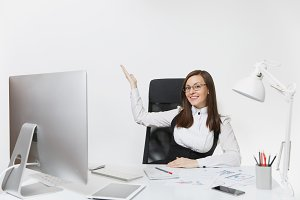 Smiling business woman sitting at the desk, working at computer with documents in light office, pointing her hand at white background with copy space for your advertisement or promotional content