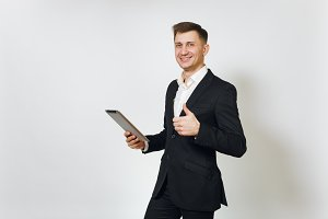 Young successful handsome business man in black suit working on modern tablet, showing thumb up isolated on white background for advertising. Concept of achievement, career and wealth in 25-30 years.
